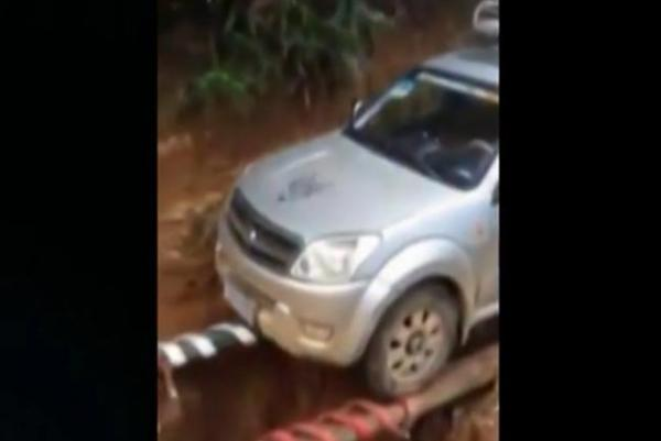 Brave-SUV-driver-crosses-collapsed-road-on-tree-trunk-chopstick-bridge